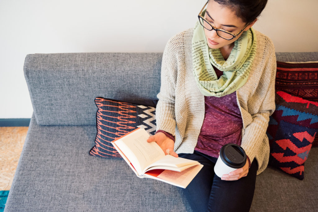 Person wearing a scarf sitting on a grey couch reading a book and holding a cup of coffee