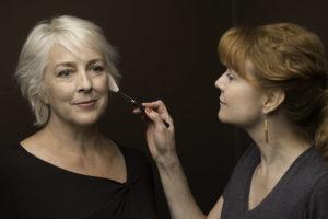 Artist applying makeup on a woman's face.