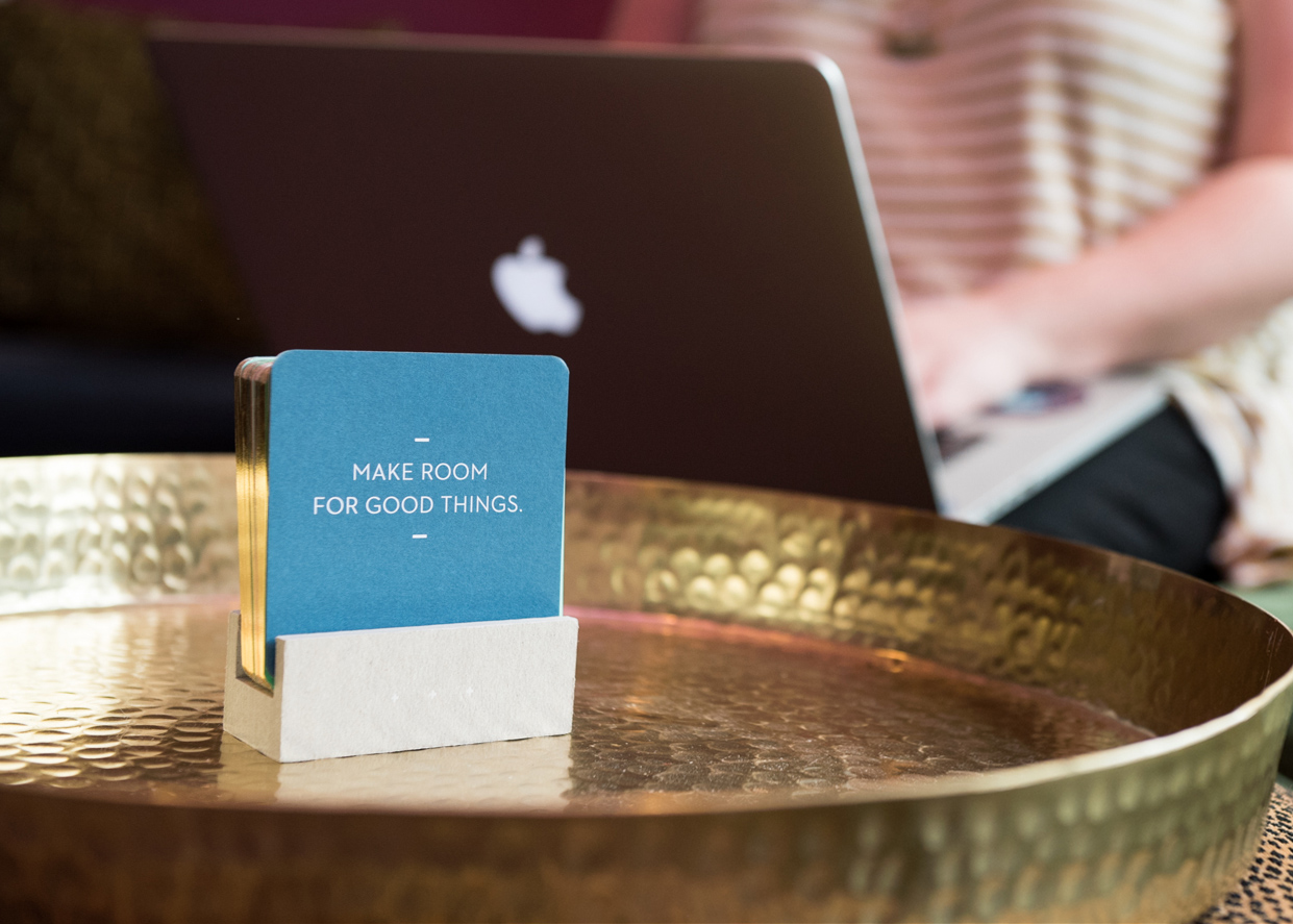 "Coasters that say ""Make Room for Good Things"" with a person working on a Macbook in the background"