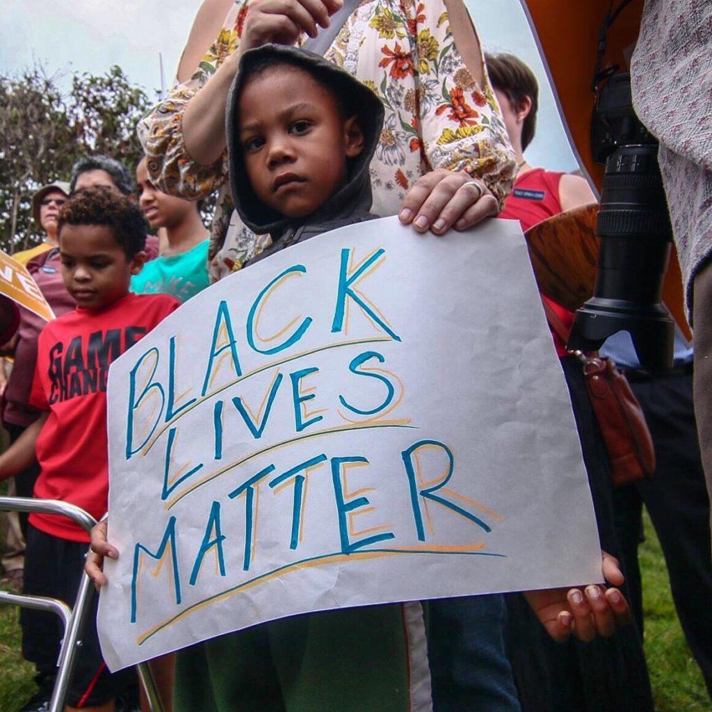"young black child holding ""Black Lives Matter"" poster"