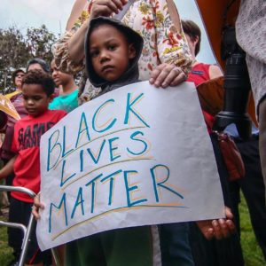 "young black child holding ""Black Lives Matter"" poster"