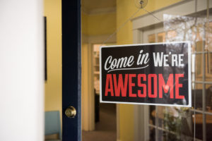 "Welcome sign hanging from post that says ""Come In, We're Awesome"""