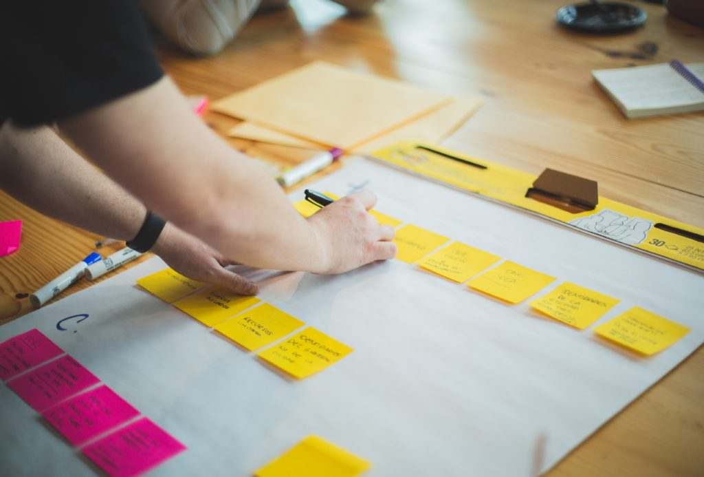 The hands of a project manager as they organize and write on post-it notes.